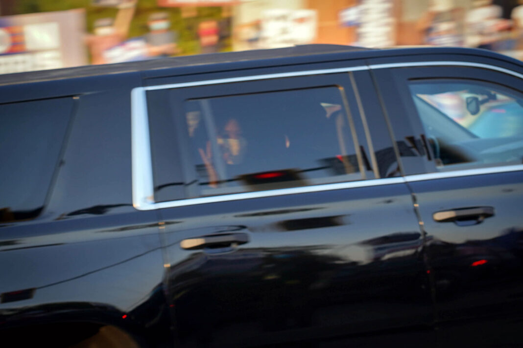 Kamala Harris waving inside a limousine