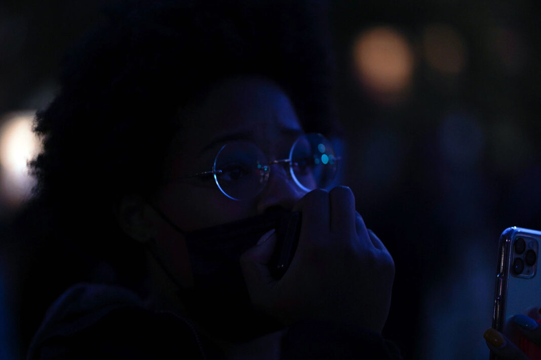 Semira X uses a microphone to speak in the darkness