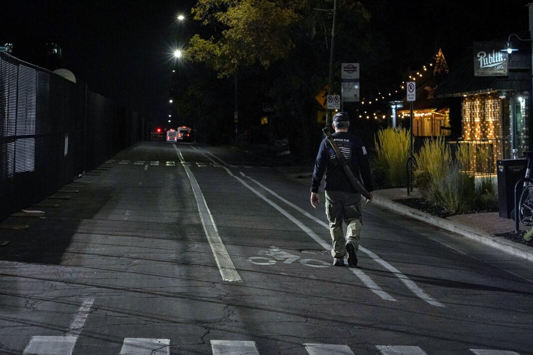 Trump supporter walks down a street at night