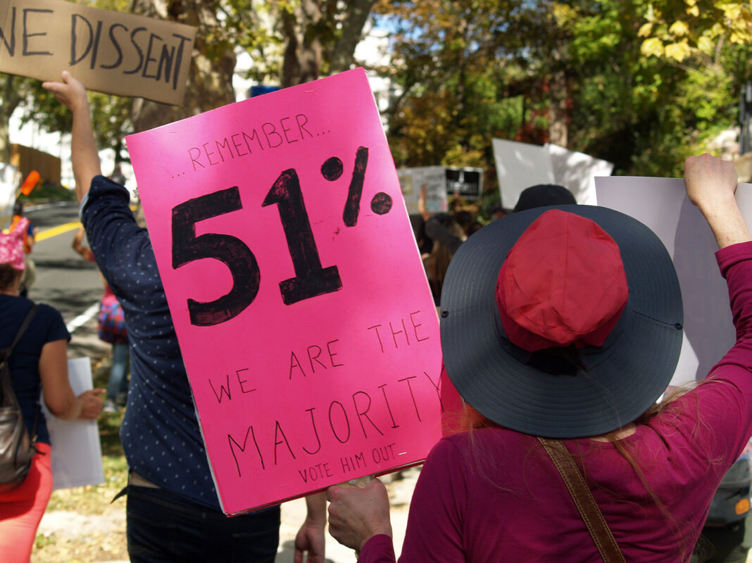 "Pink signs that reads ""Remember 51% we are the majority vote him out"""
