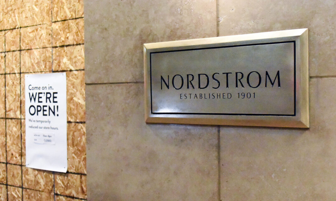 Nordstrom sign next to door covered in plywood