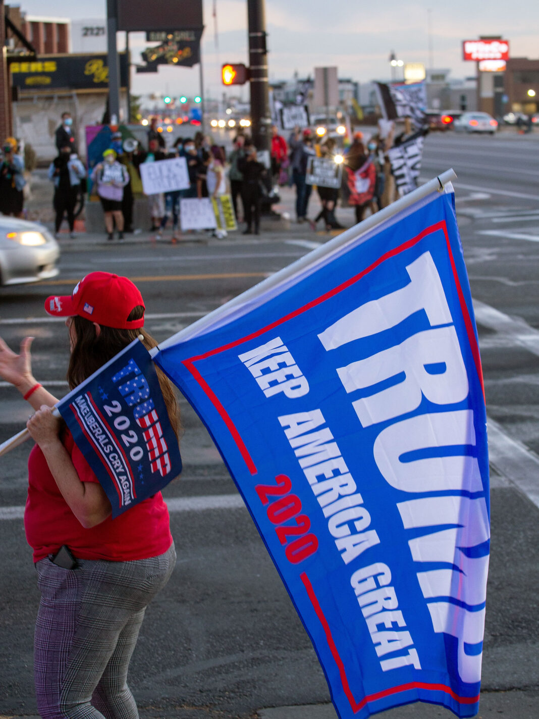 Buffy Yaple holding two Trump flags
