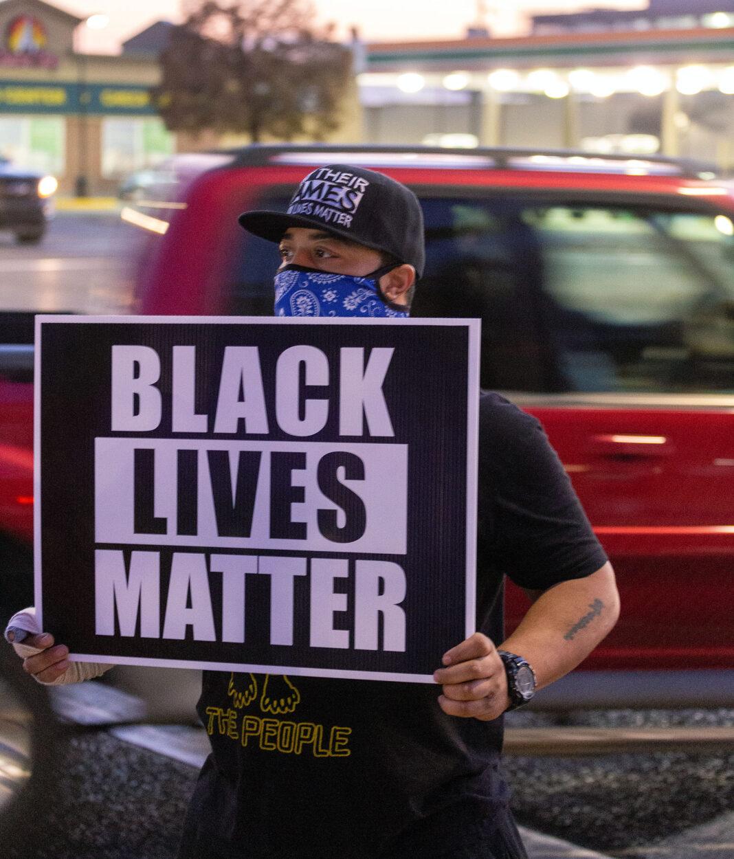 Kayjay holds Black Lives Matter sign