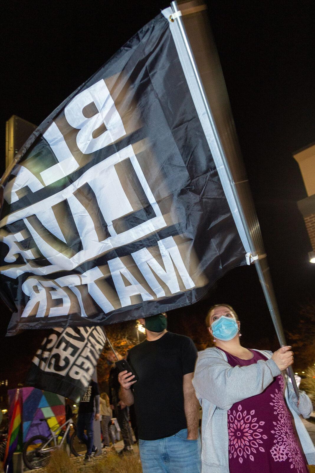 Masked demonstrator waves Black Lives Matter flag