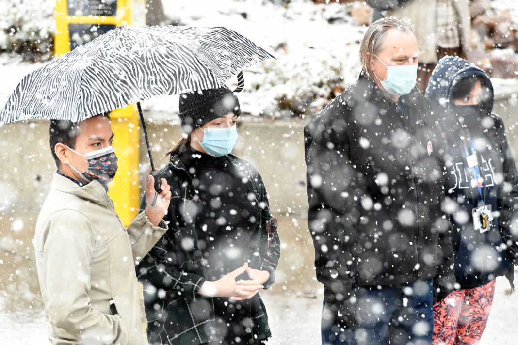 Masked spectators wait in snowy weather