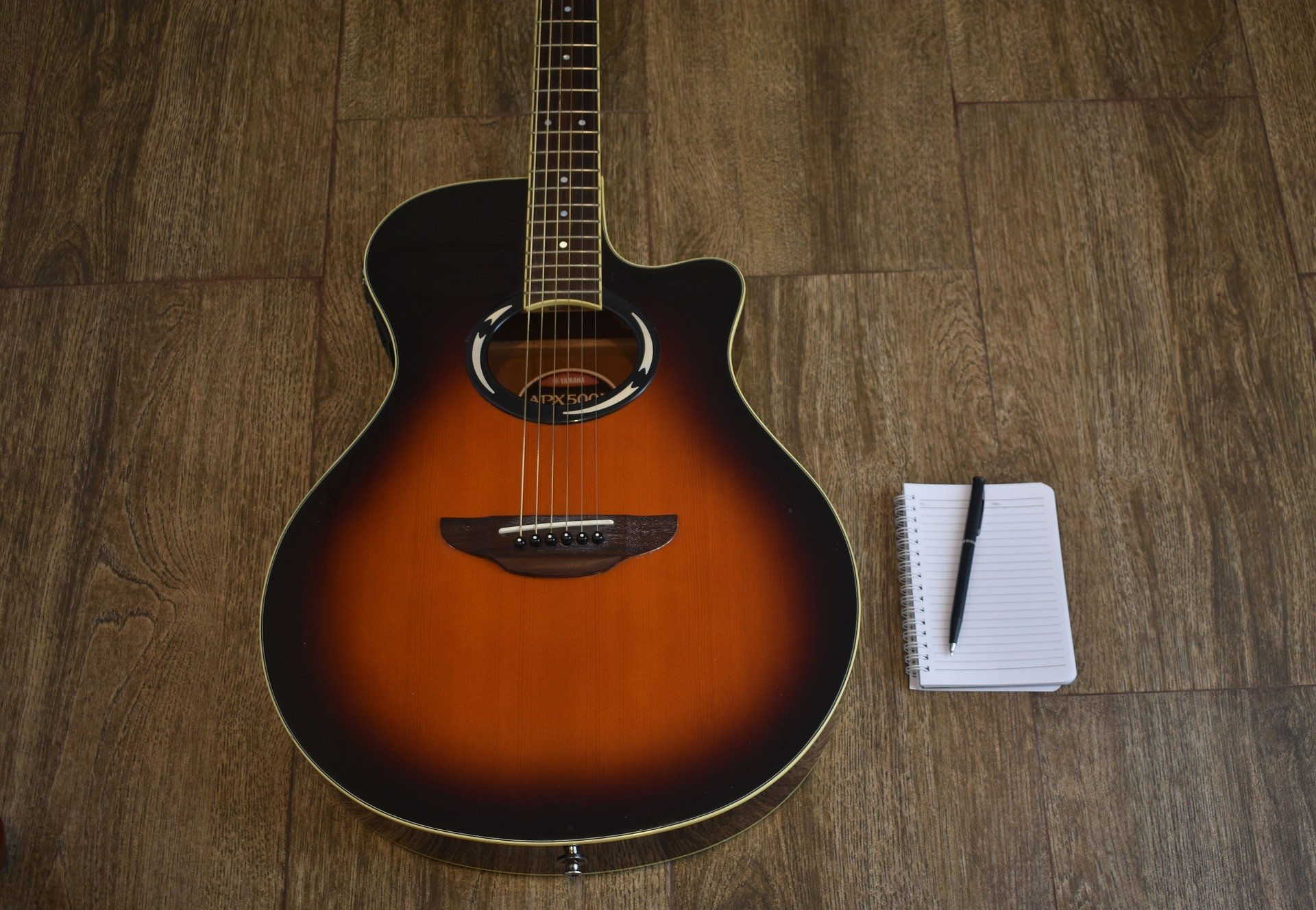 Blank notepad lying next to guitar