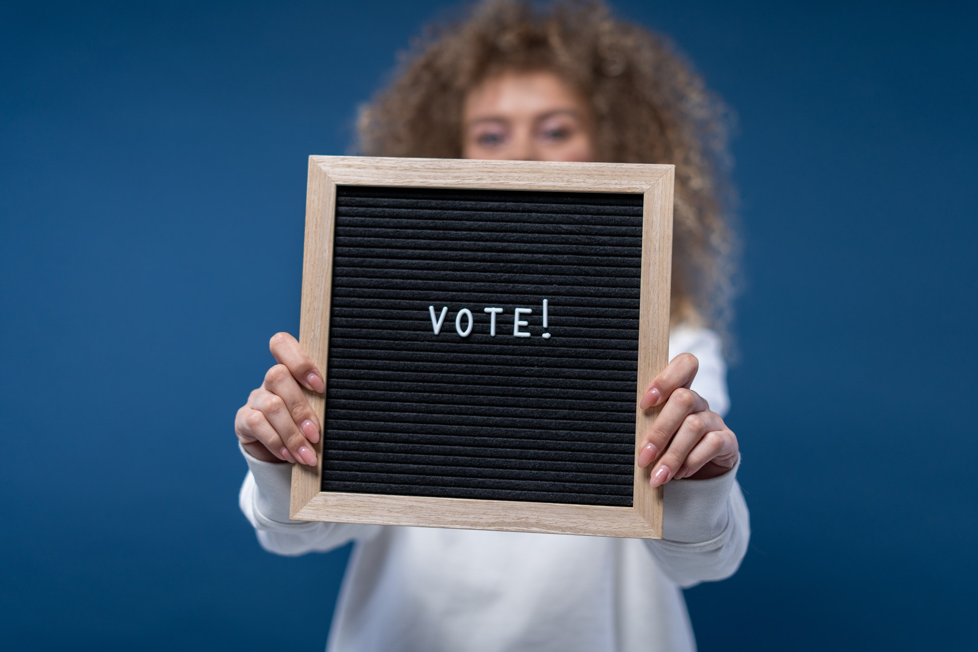 """Person holding a """"Vote!"""" sign"""