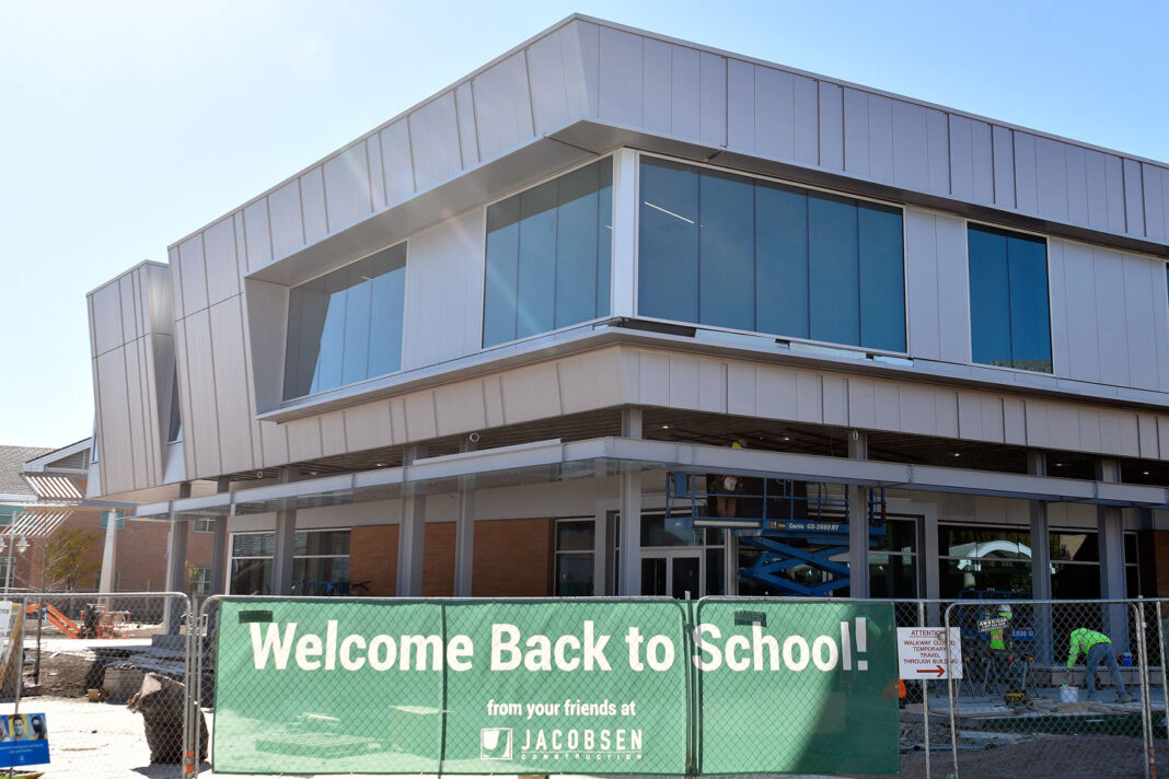 """Sign in front of new student center under construction reads """"Welcome back to school!"""""""