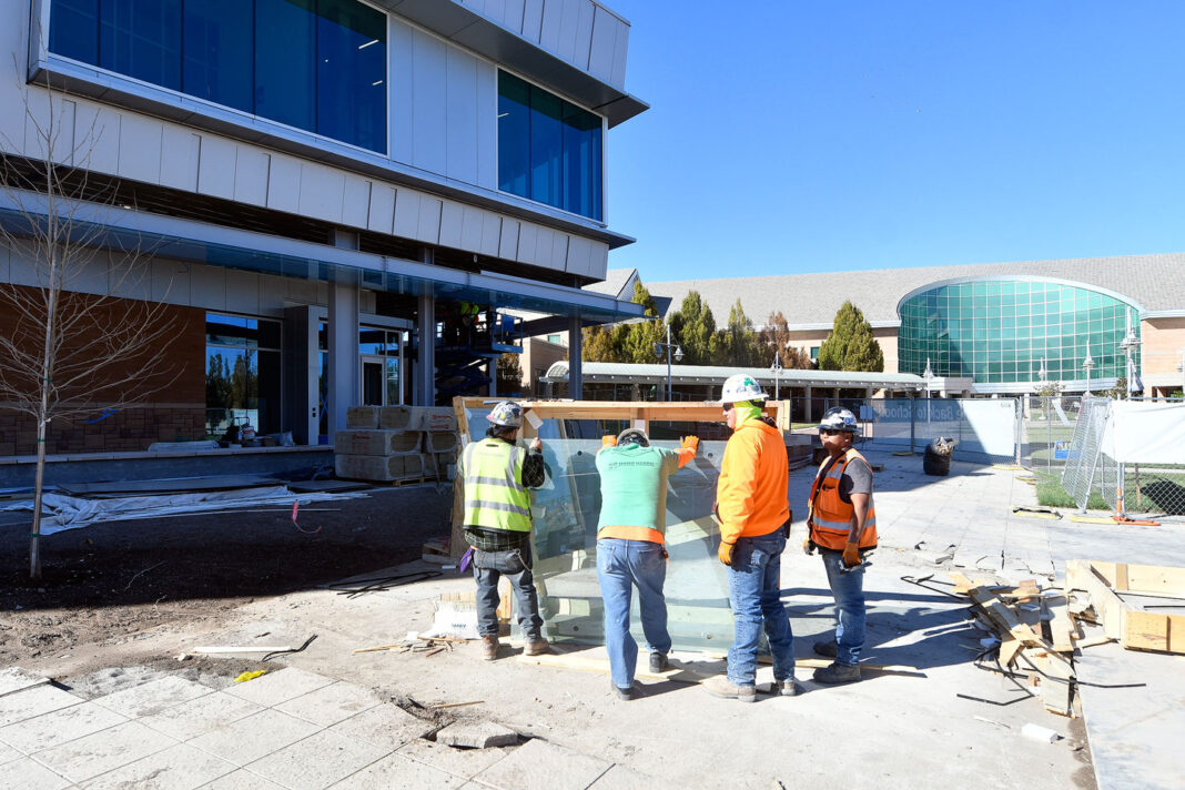 Four construction workers hold a sheet of glass