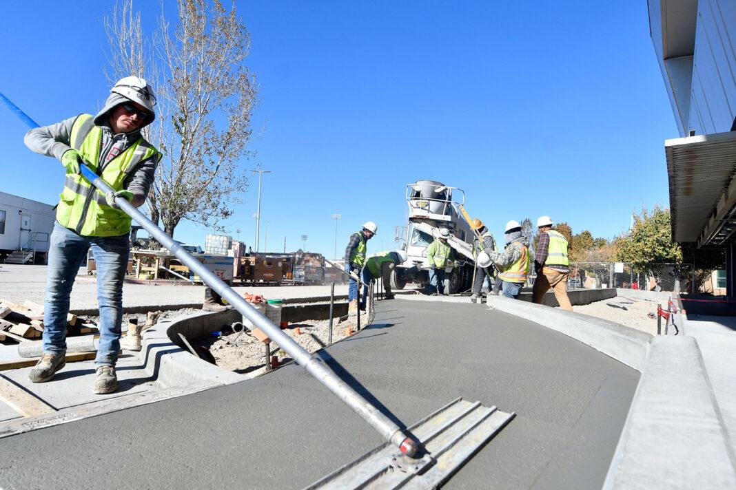 Construction worker brooms fresh concrete