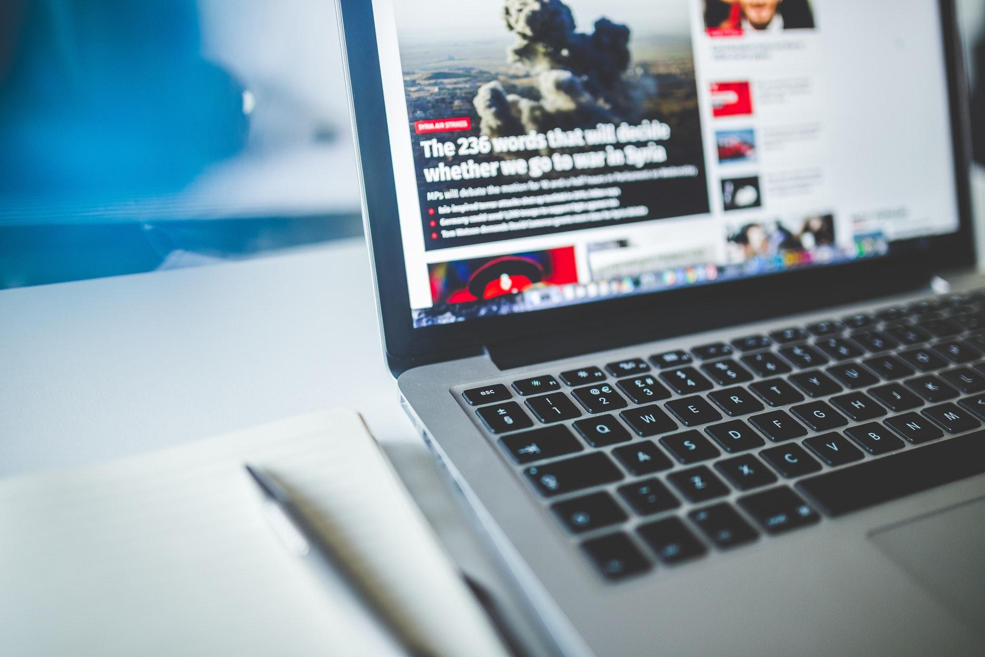 News website on gray laptop next to journal