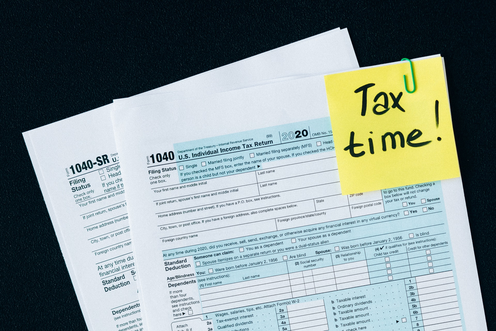 """""""Tax time!"""" sticky note with 2020 tax forms"""