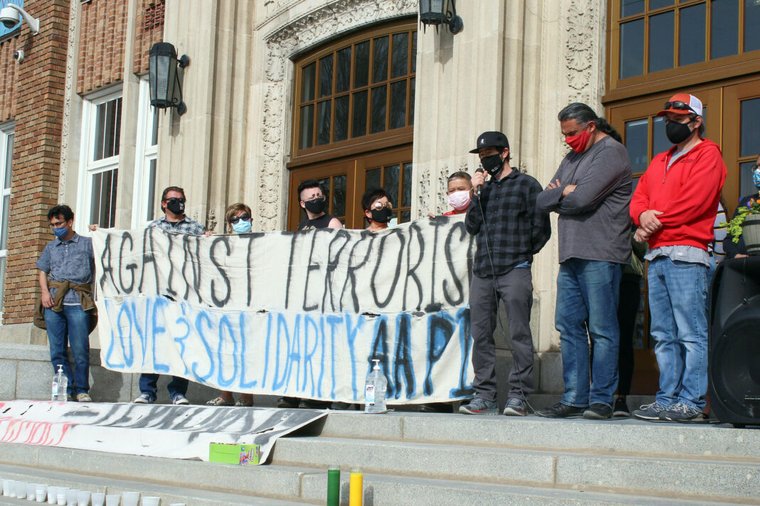 """Vigil attendees holding banner that reads """"Against terrorism - love and solidarity AAPI"""""""