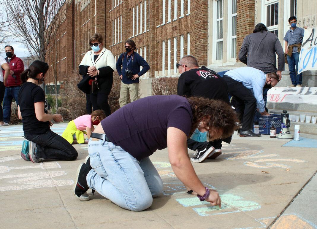Timothy Davis writing with chalk on the sidewalk