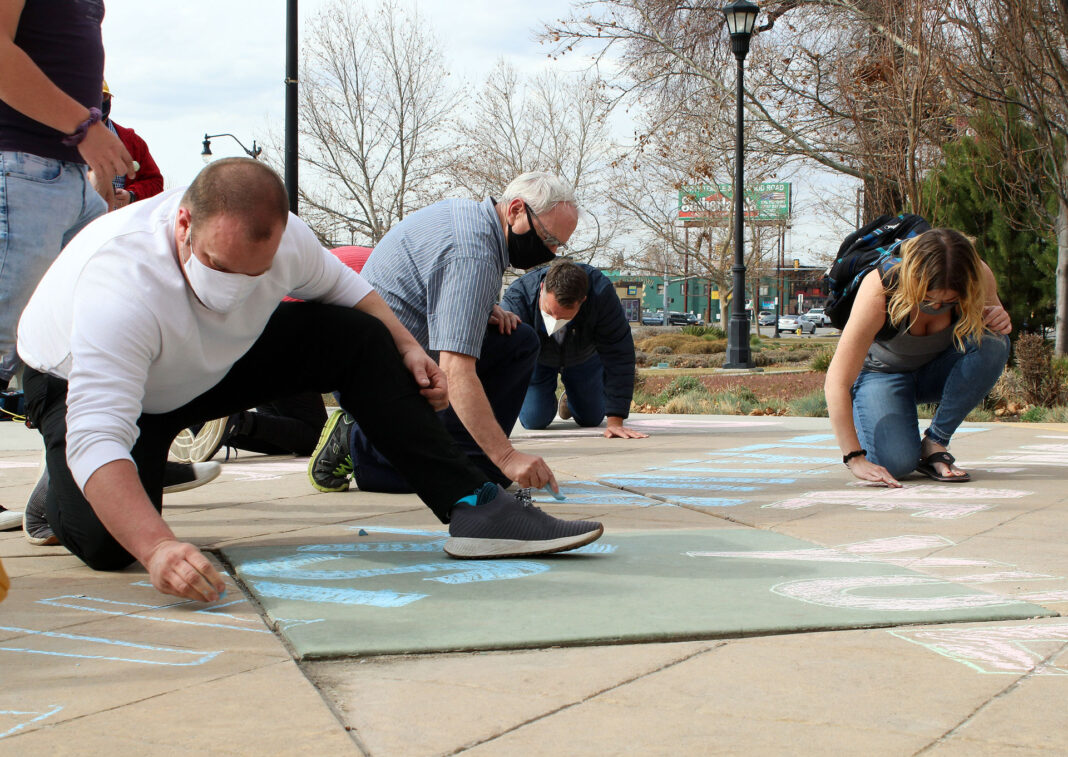 People writing names in chalk on a sidewalk