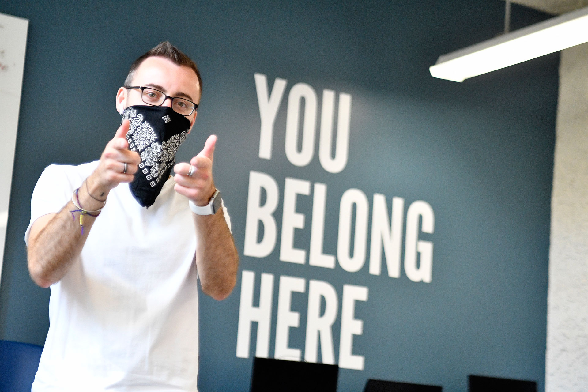 """Peter Moosman stands in front of wall that reads """"You belong here"""""""