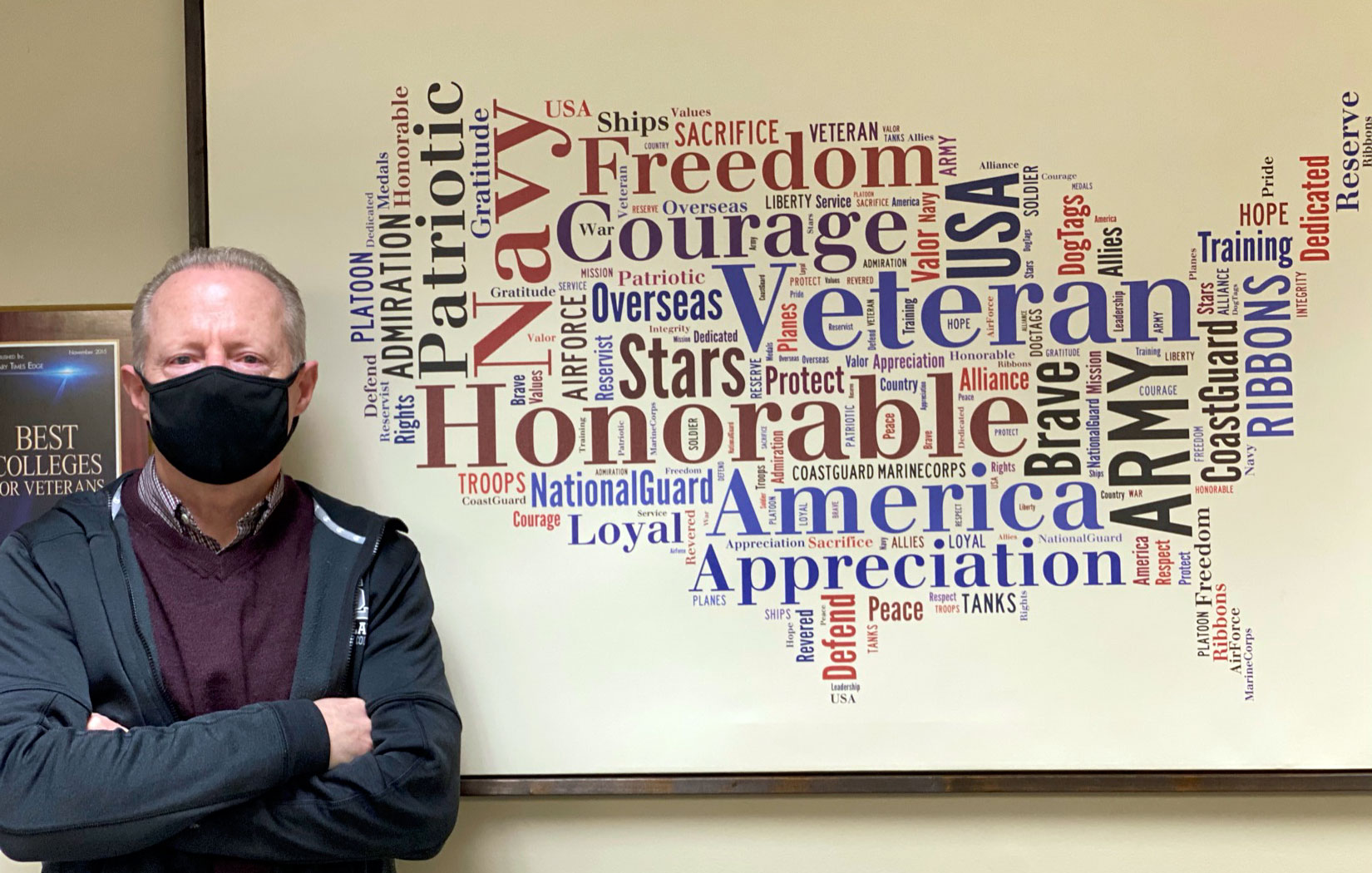 Steve Hill stands next to military word cloud shaped like United States