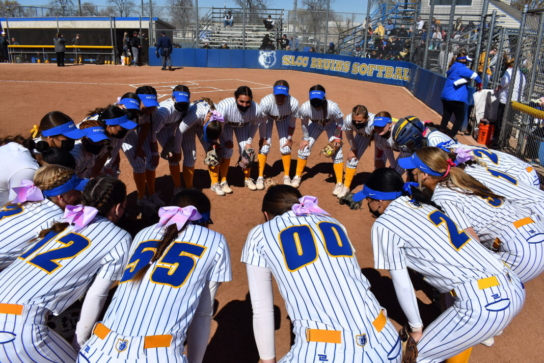 Softball players huddle in a circle