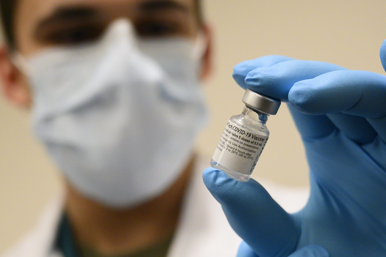 Army Spc. Angel Laureano holds a vial of the COVID-19 vaccine