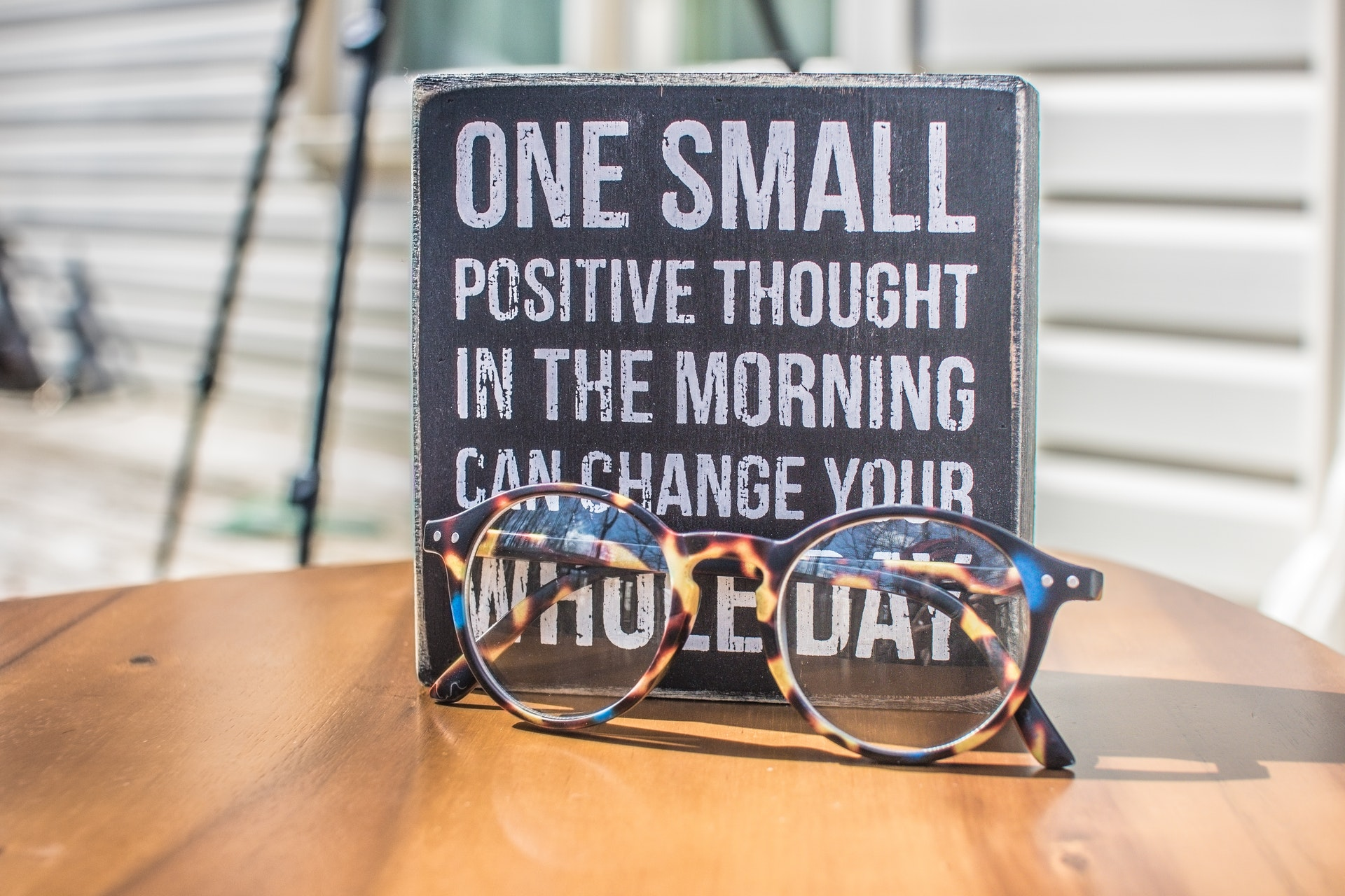 """Glasses with sign that reads """"One small positive thought in the morning can change your whole day"""""""