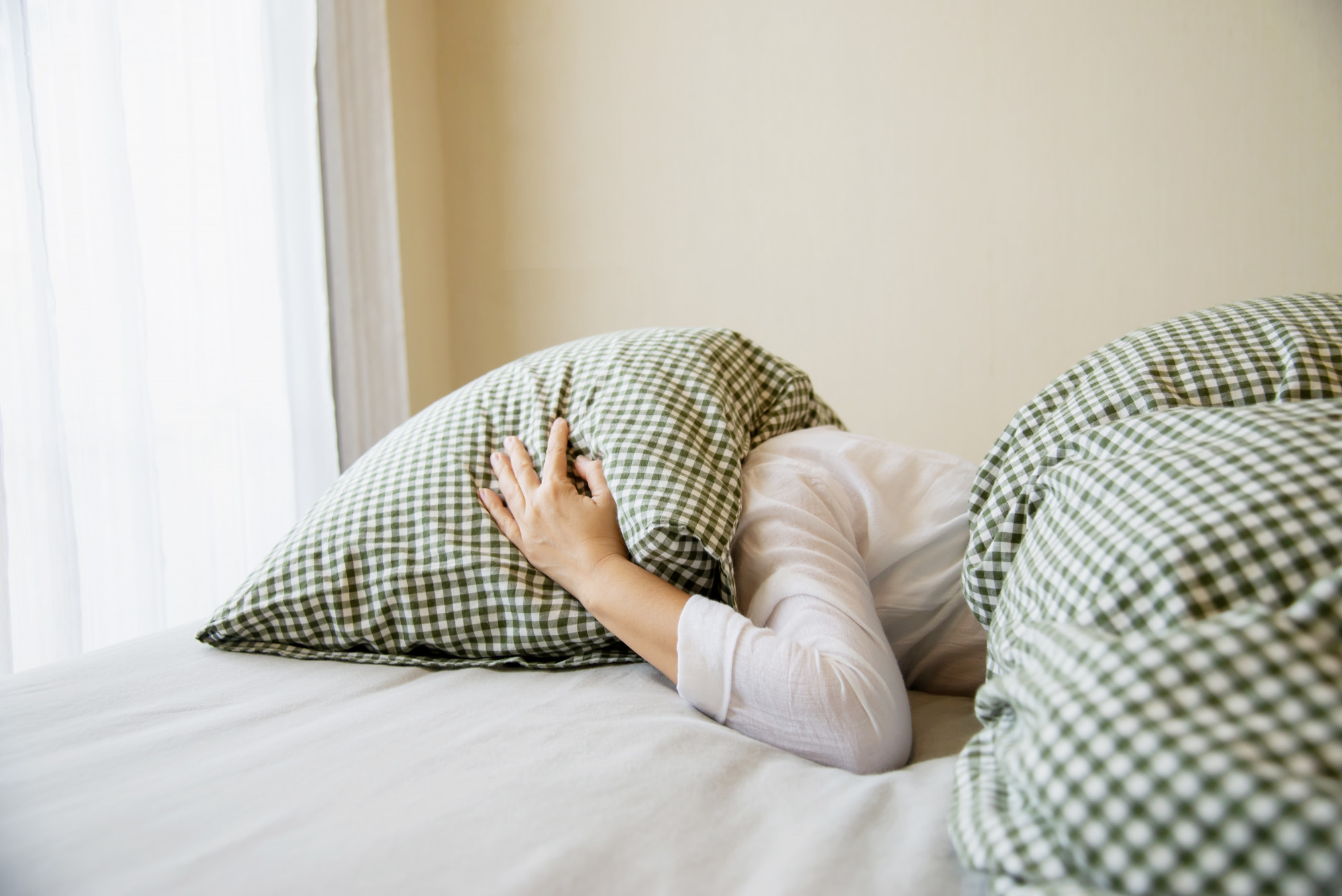 Woman covers her head with a pillow while in bed