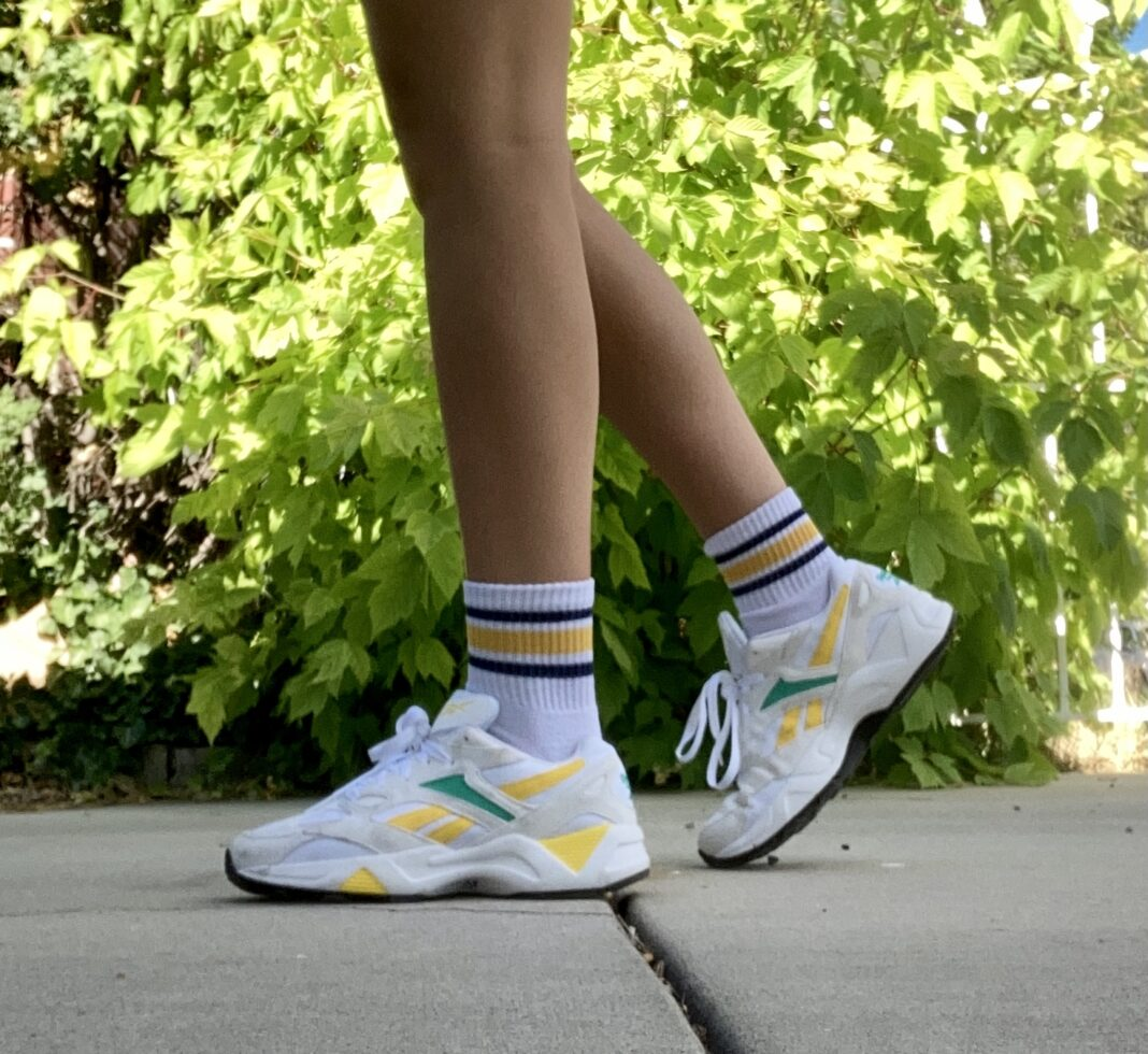 Person wearing white socks and shoes with yellow and blue trim