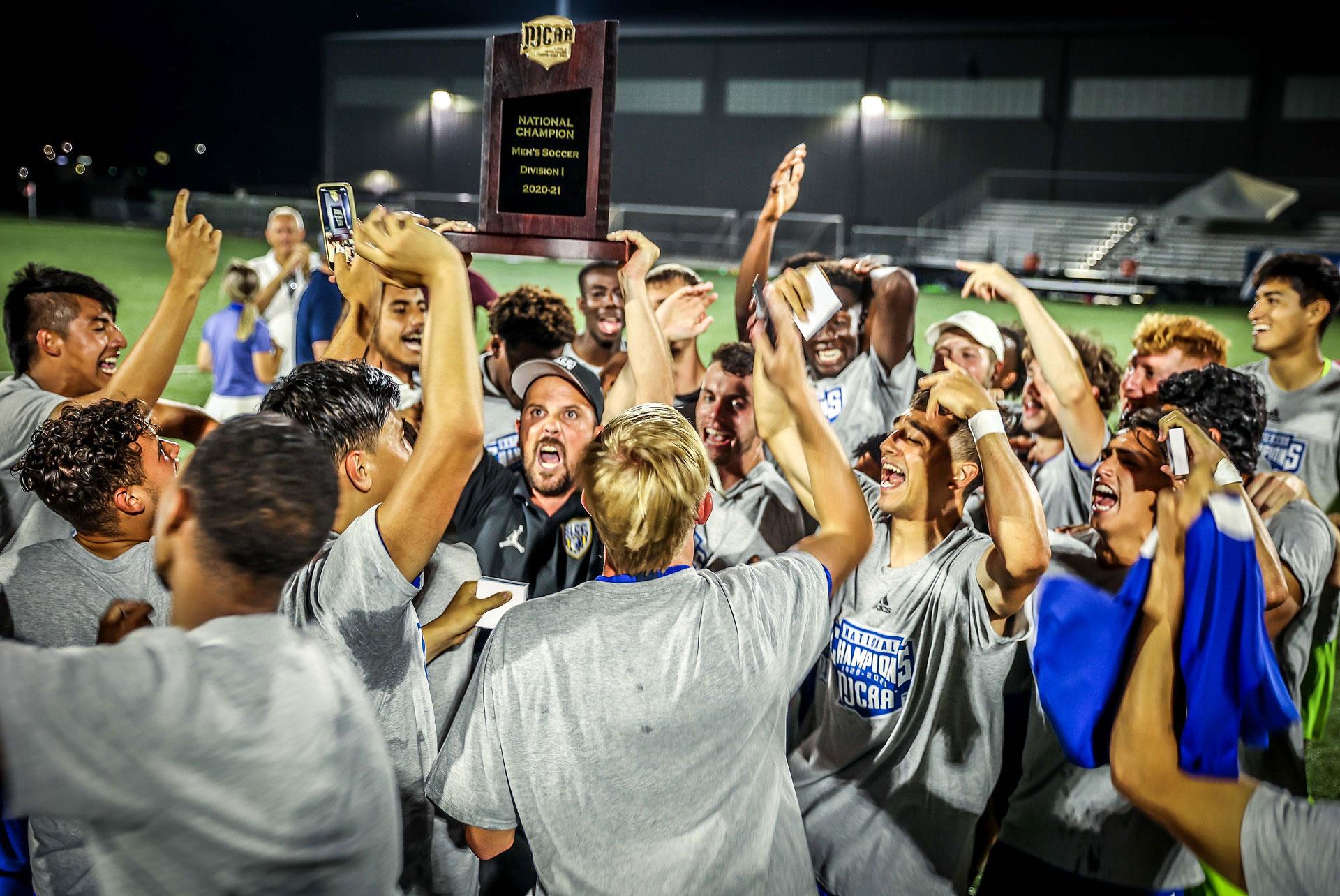 Coach Davis hoists trophy as players celebrate