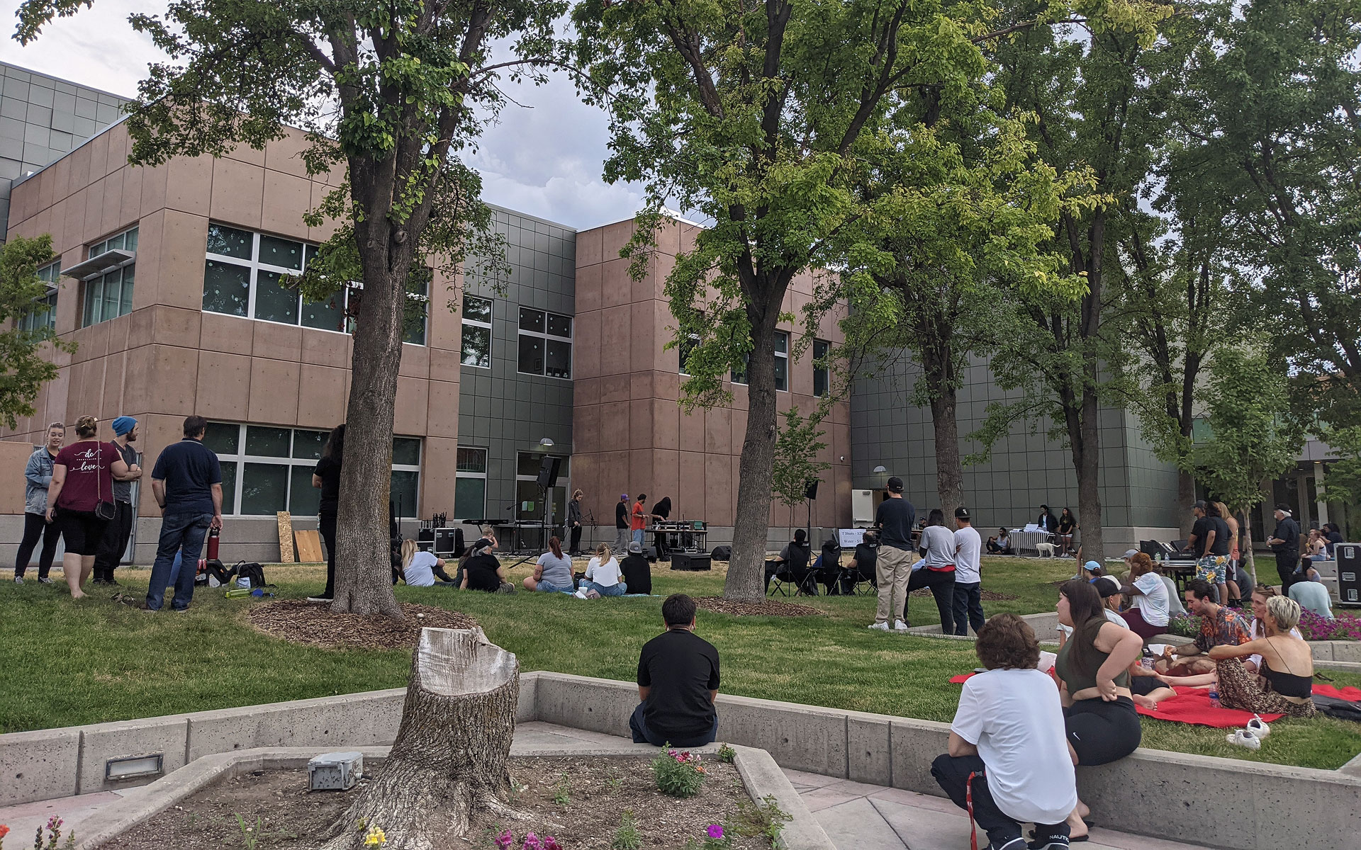 Dozens of people sit outside listening to live music