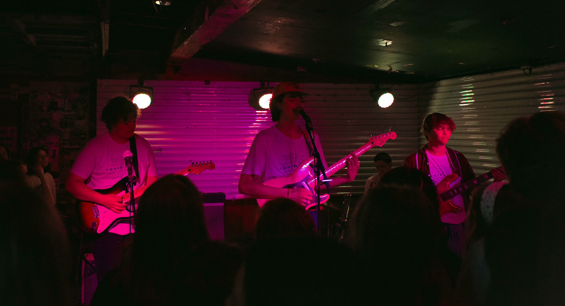 Three band members play guitar in front of live audience