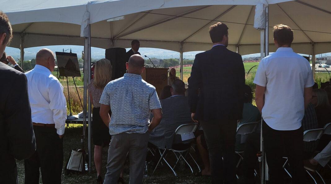 Man speaks at podium to large crowd