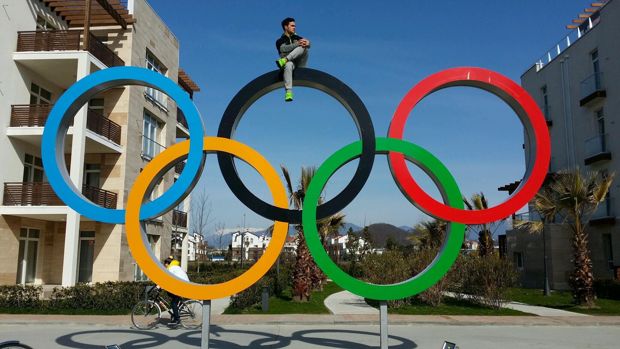 Eddy Alvarez sitting on top of Olympic Rings