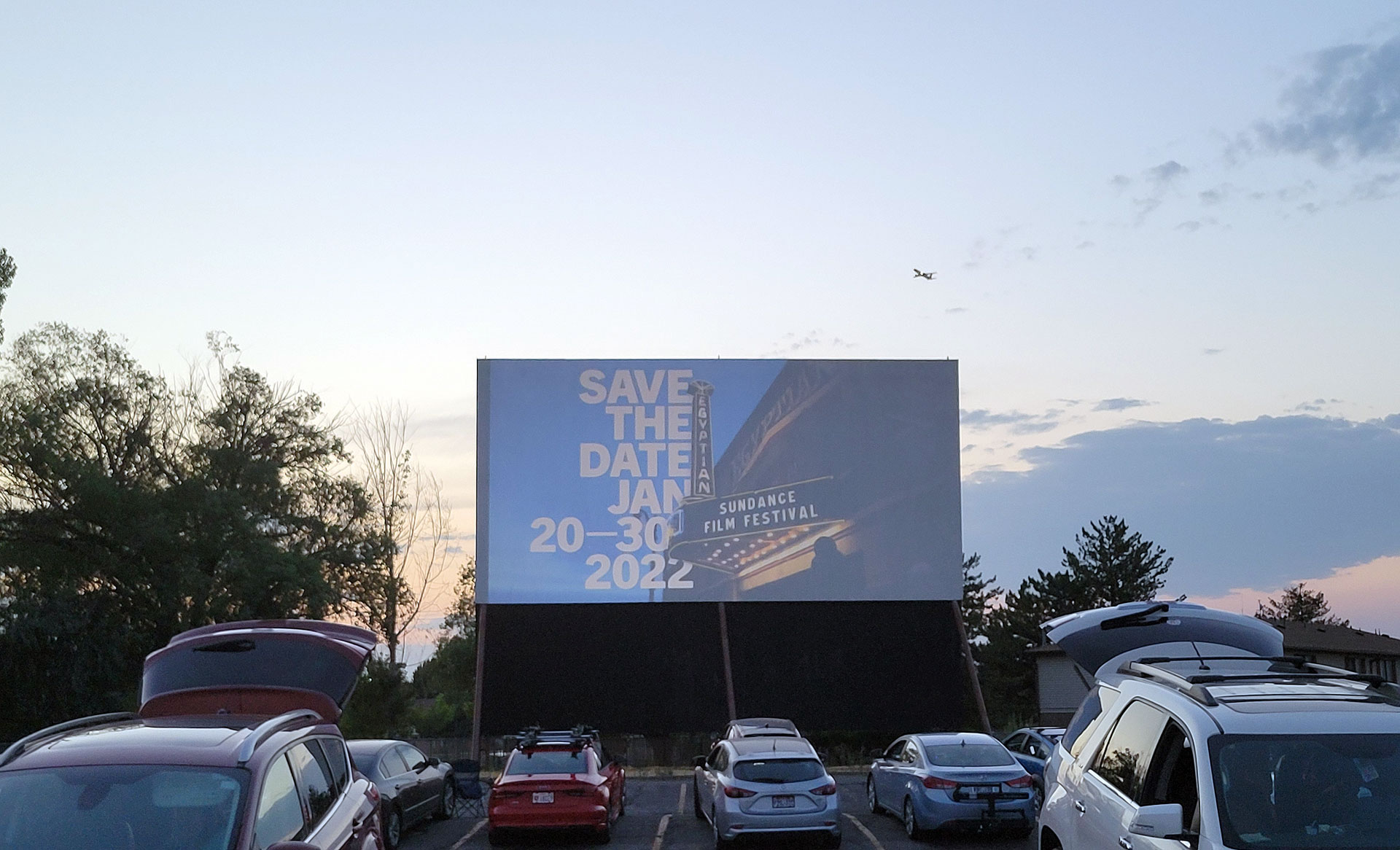 Cars parked in front of giant projection screen
