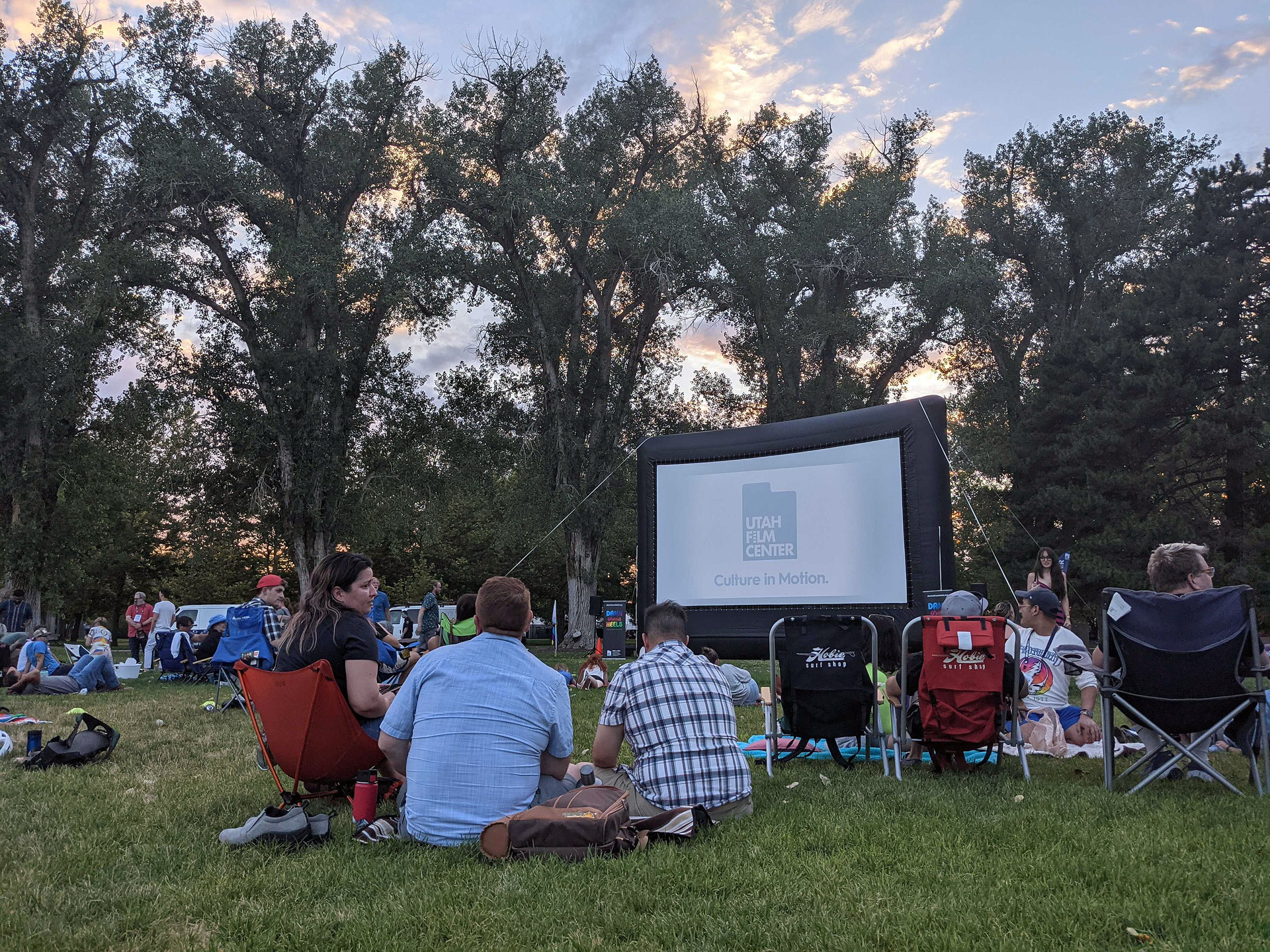 Dozens of people sit outside to watch a movie