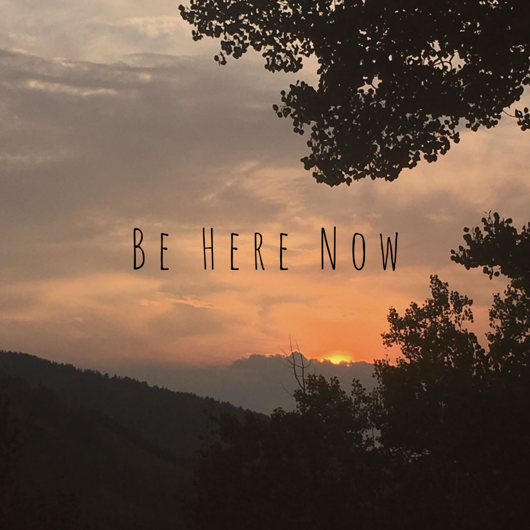 """View of a red cloudy sky with the words """"Be Here Now"""""""
