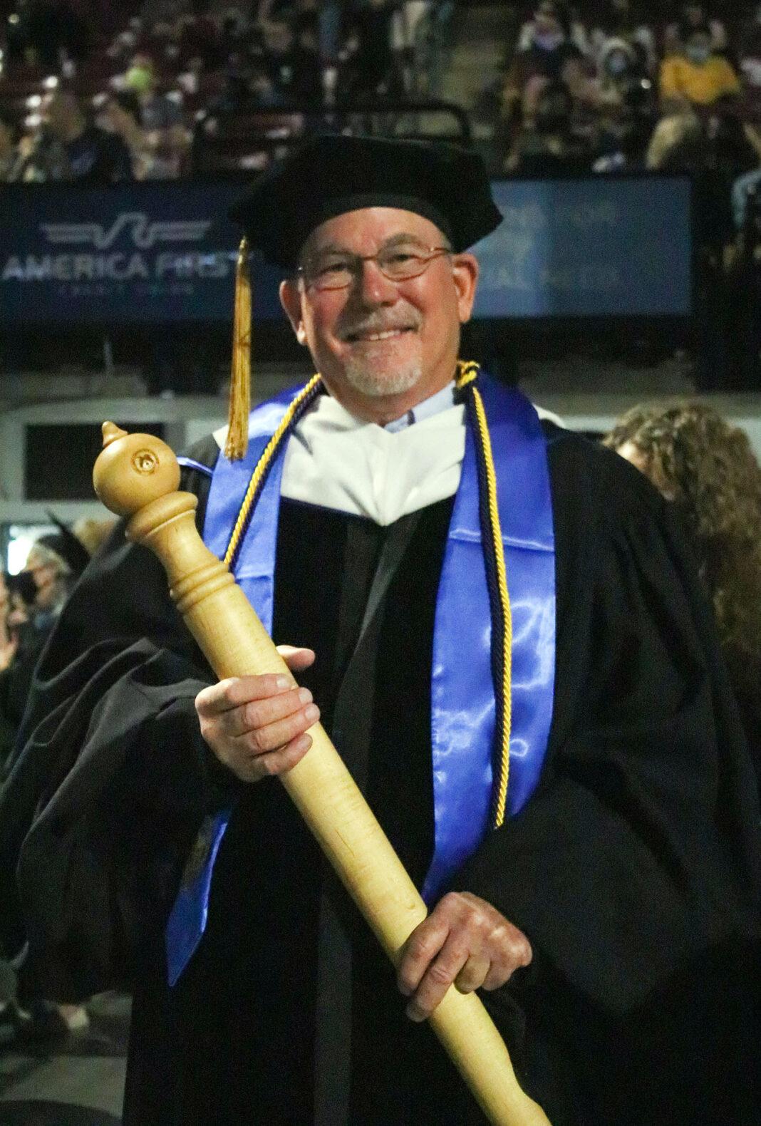 Brett Baird holds a ceremonial mace
