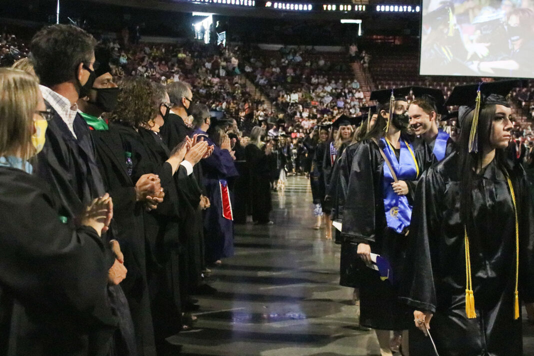 Graduates walk past faculty members