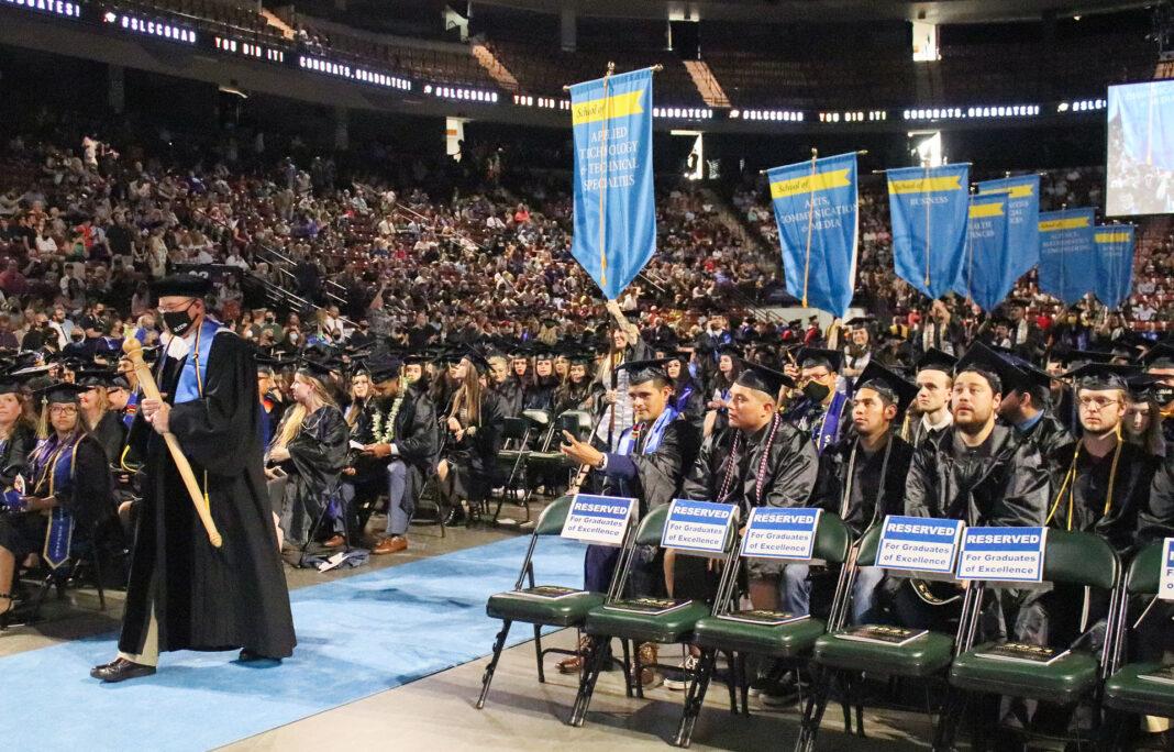Brett Baird walking ahead of graduates