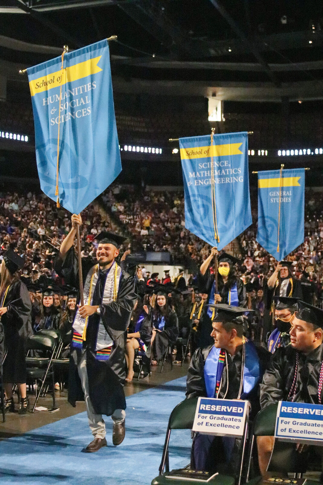 Graduates of Excellence carrying banners