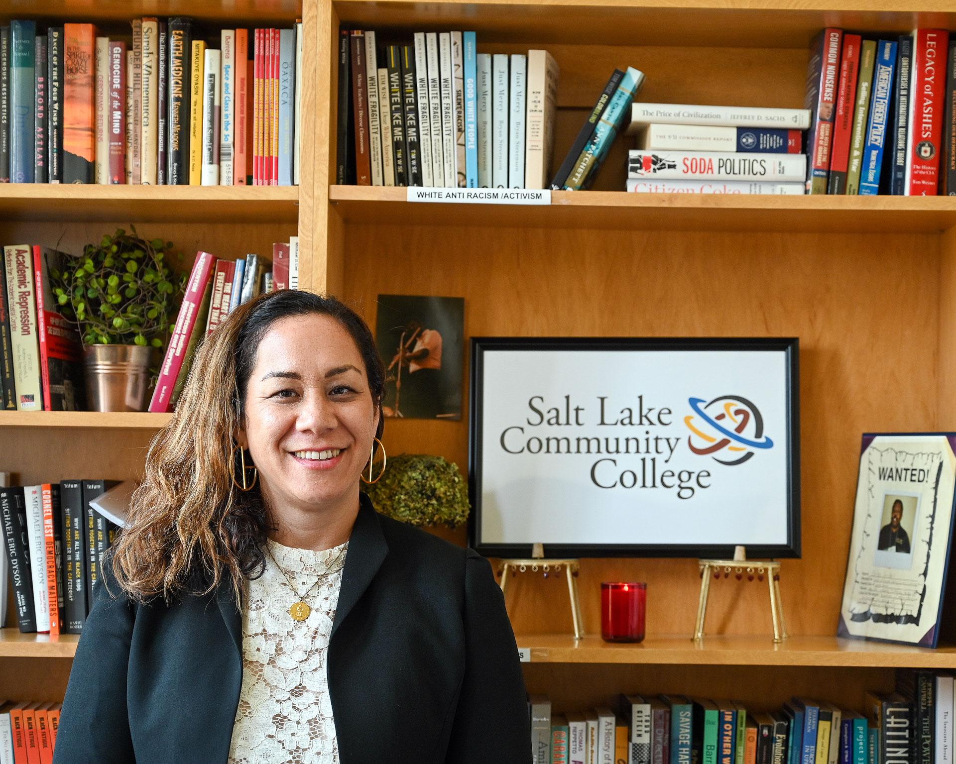 Dr. Kinikini stands next to SLCC sign on bookshelf