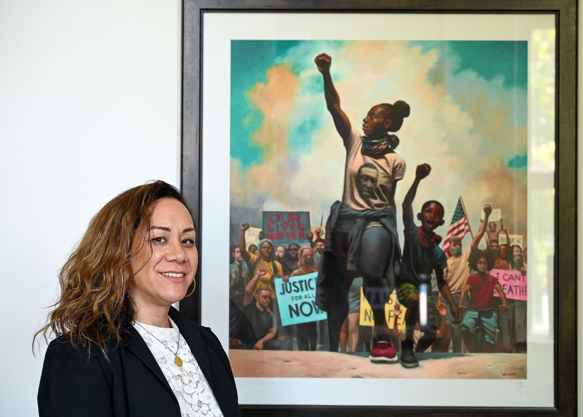 Dr. Kinikini stands next to Black power painting