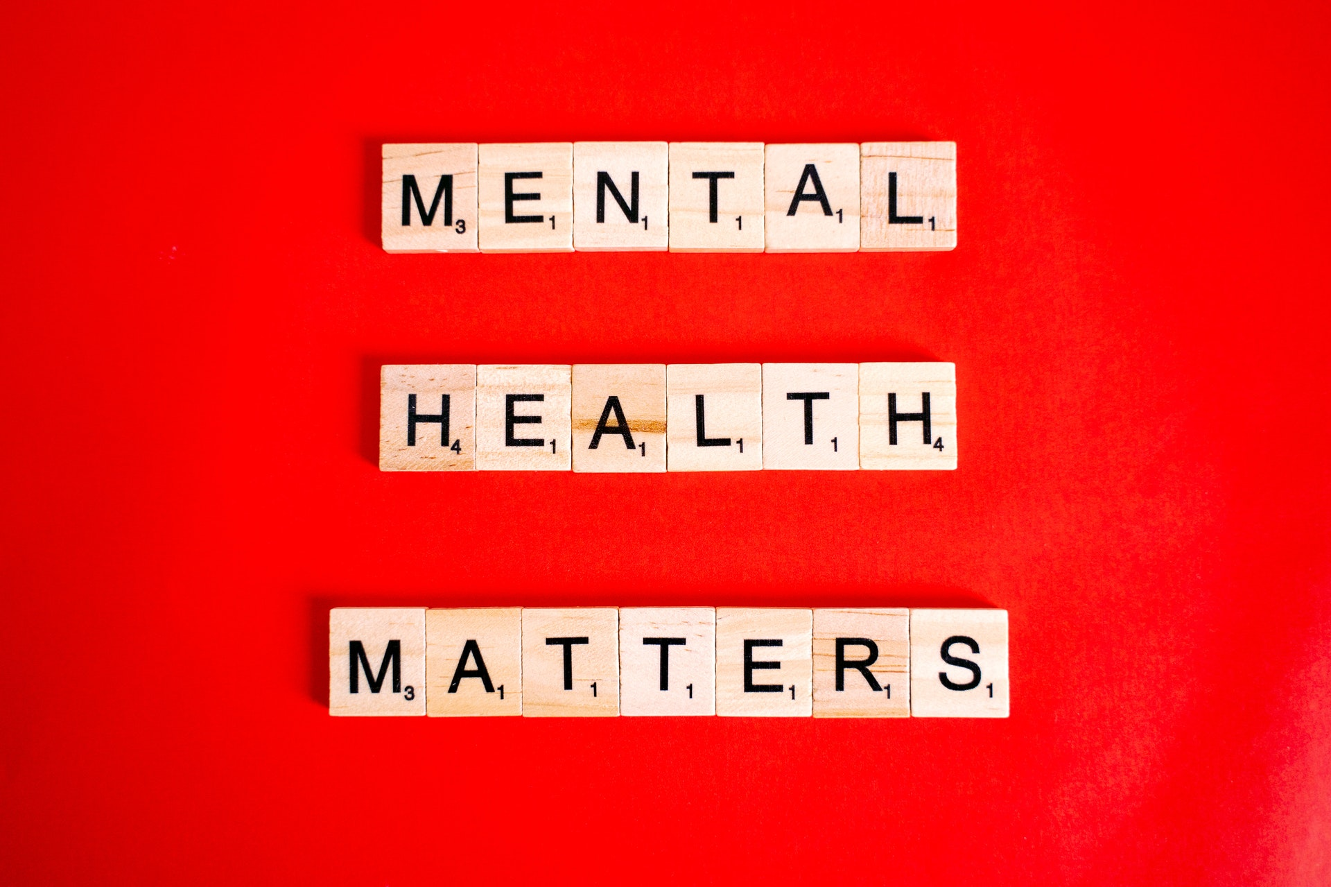 """Scrabble letters spell """"Mental Health Matters"""" on red background"""
