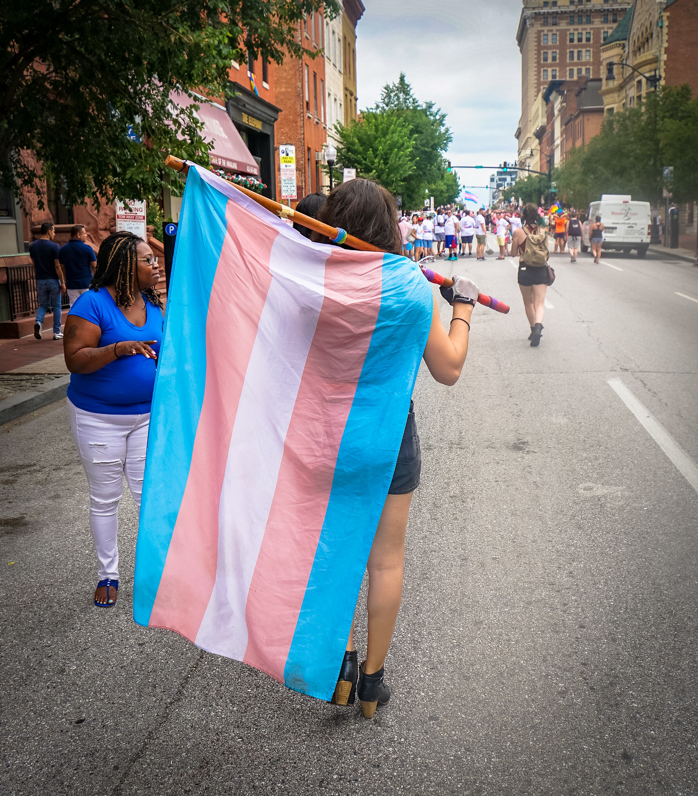 Person walking with transgender pride flag during Baltimore Pride event