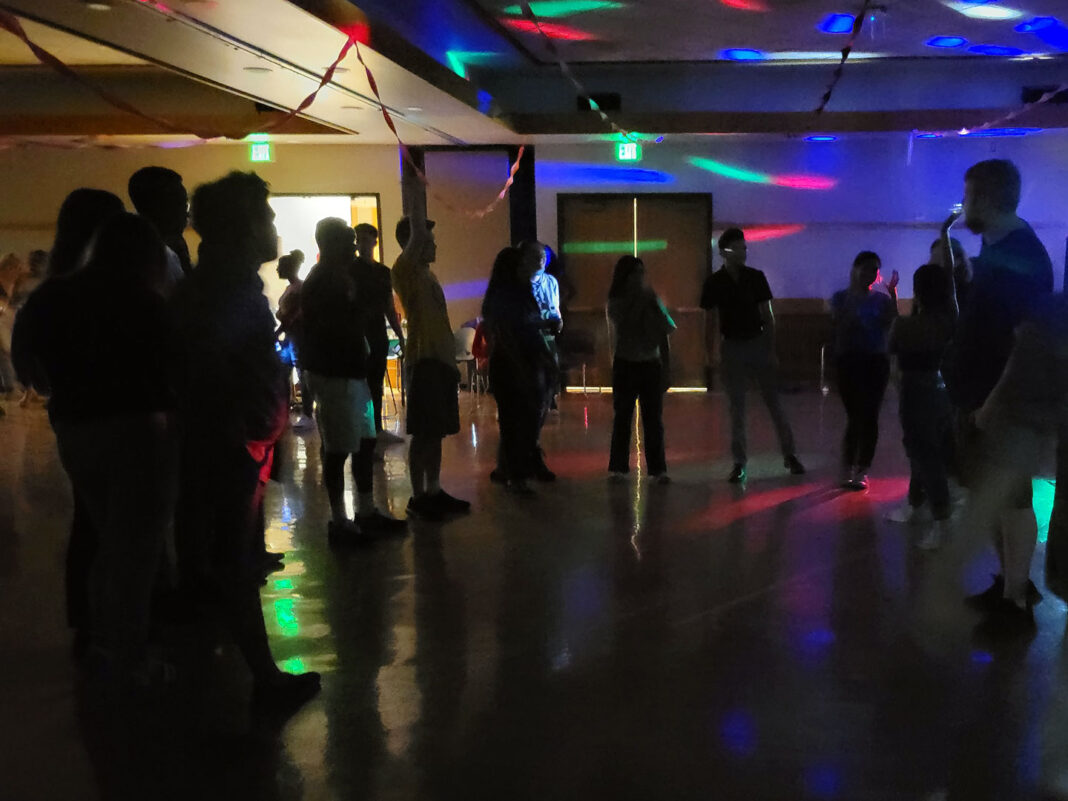People gather in a half-circle to dance