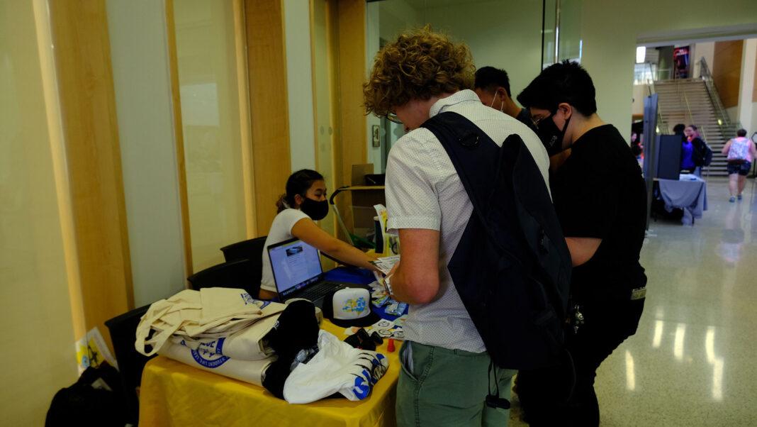 Students talk to Christina at Thayne Center table