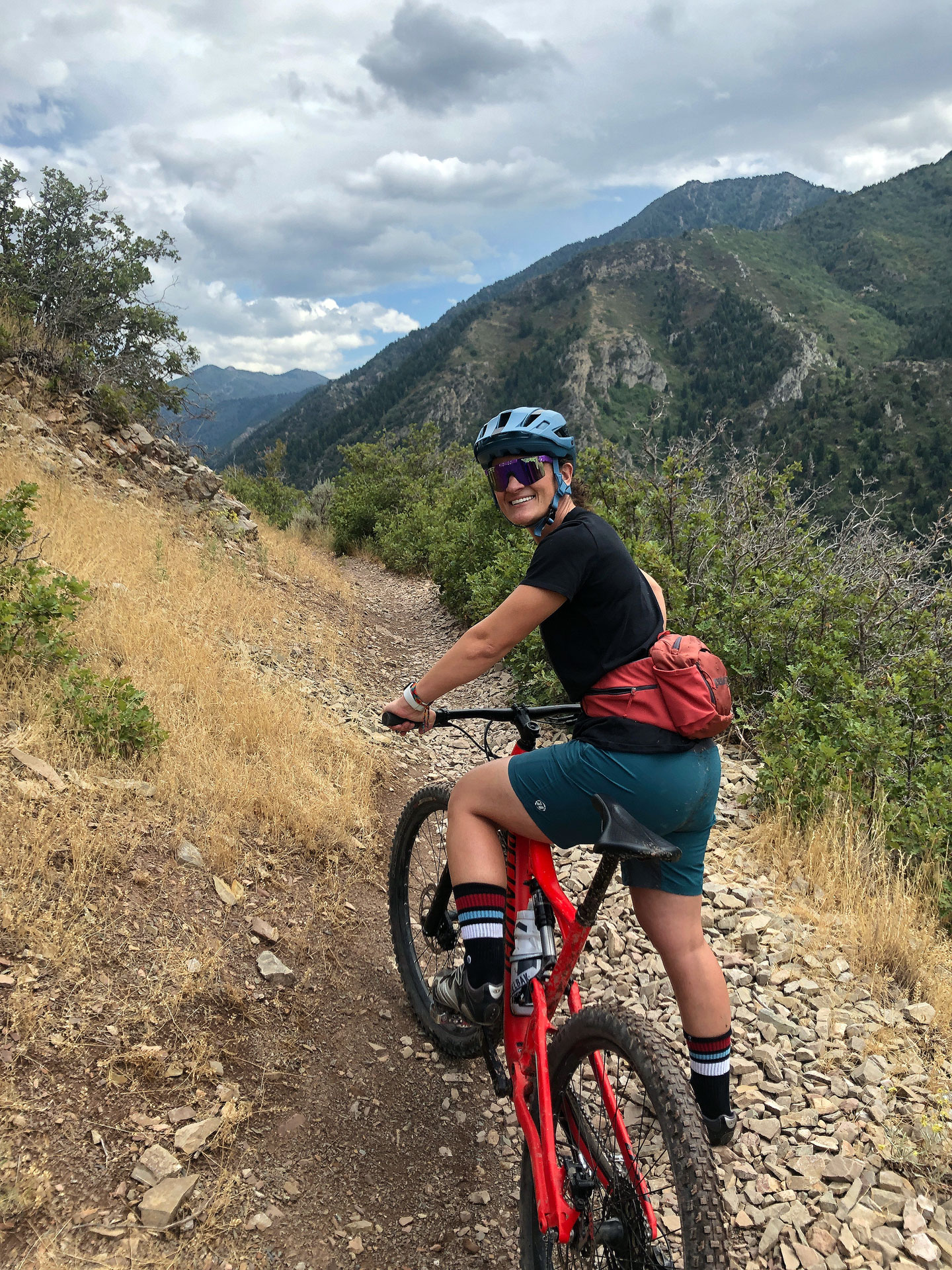 Sarah Reale looking back while sitting on a mountain bike, heading up a trail