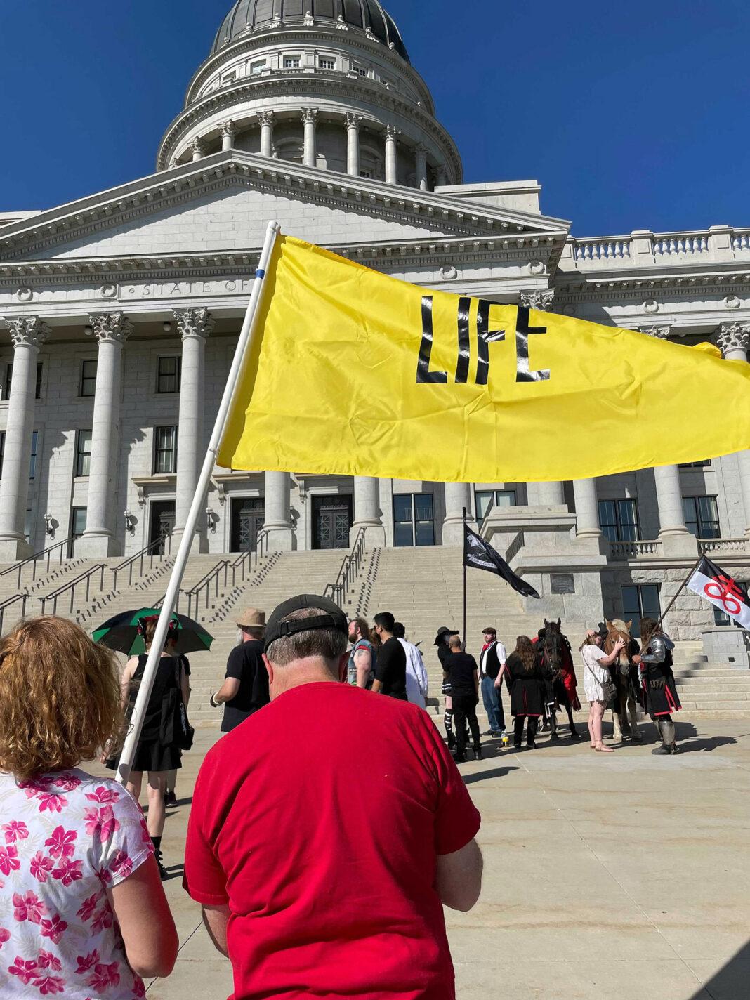 """Woman waves yellow """"life"""" flag at Utah Capitol"""