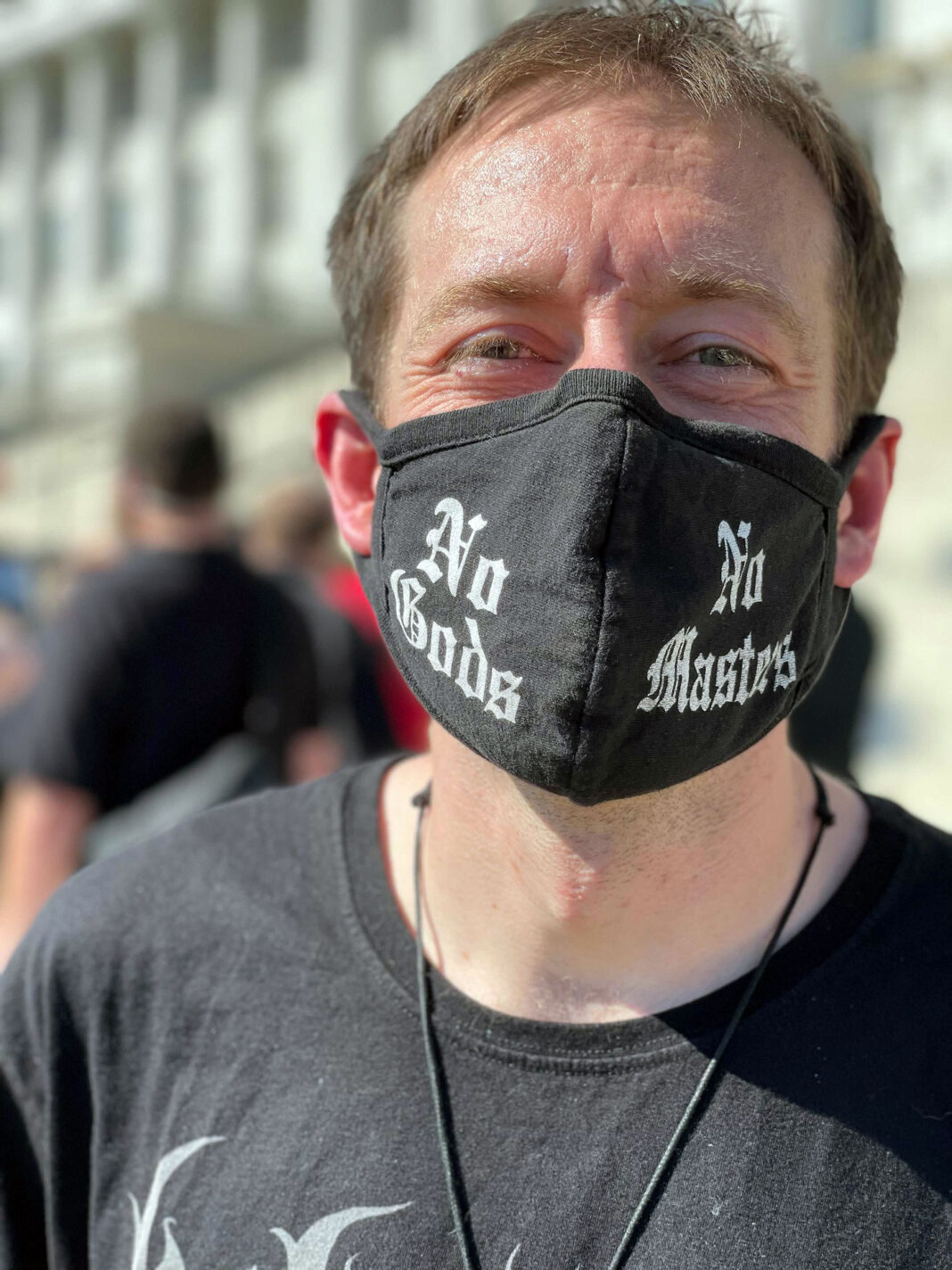 """Man wearing a mask that reads """"No Gods, No Masters"""""""