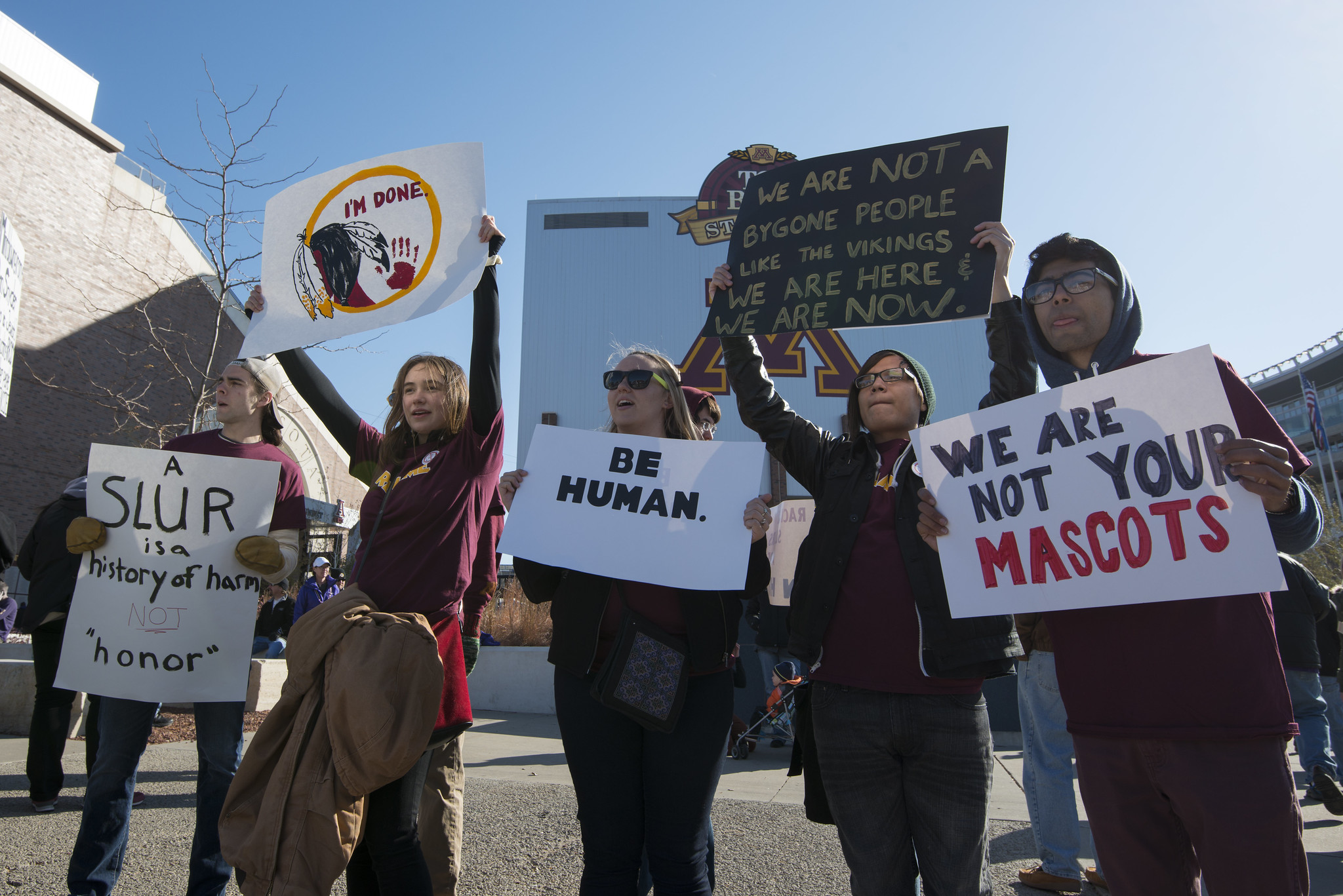 Multiple protesters hold signs denouncing Washington Redskins