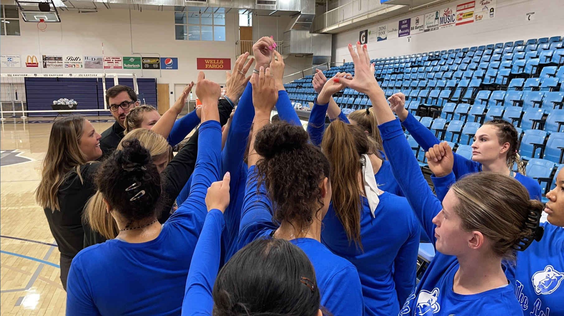 Volleyball players huddle together with raised hands