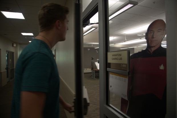 Jake Angell enters the Animation and Gaming Lab as a cardboard standee of Captain Jean-Luc Picard looks on.